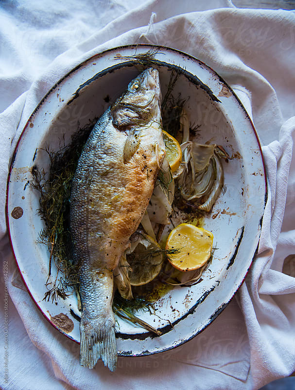 Fish baked in an old metal tray by Marta Muñoz-Calero Calderon for Stocksy United