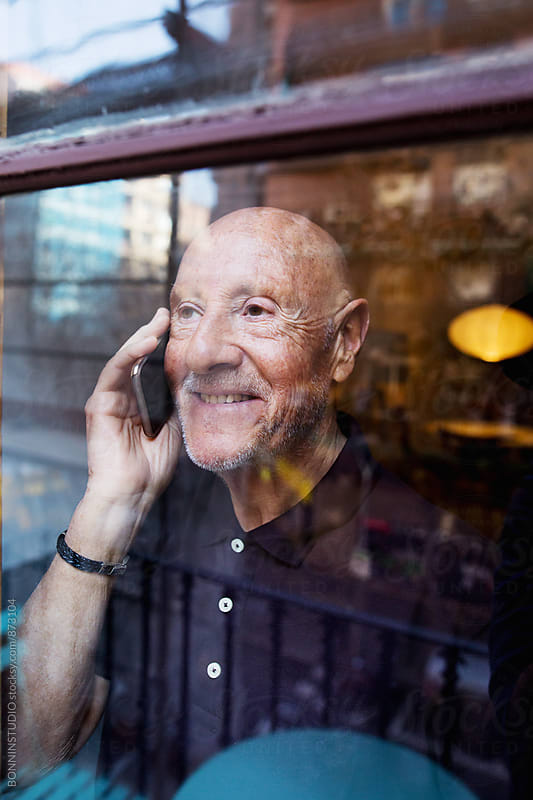 Elderly man looking through the window talking on phone. by BONNINSTUDIO for Stocksy United