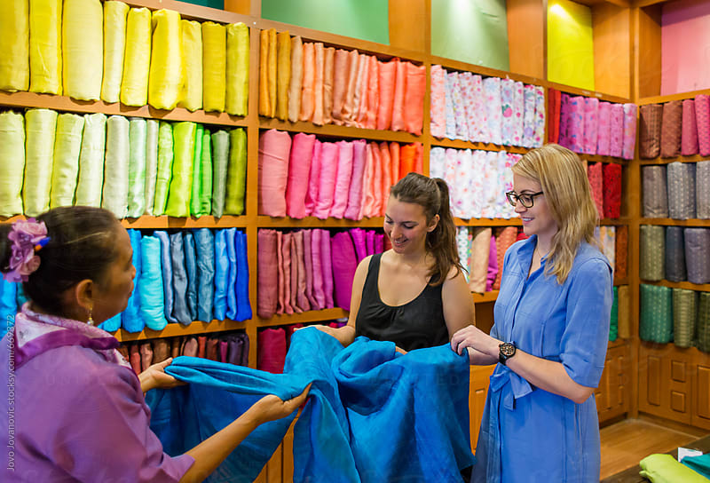 Two ladies shopping for Thai silk by Jovo Jovanovic for Stocksy United