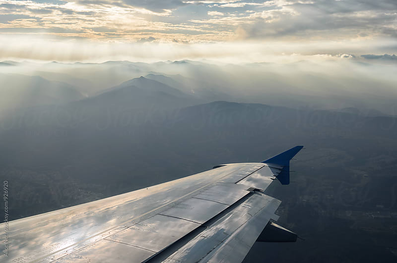 Airplane wing above mountains drawning in stunning sunrays by Alice Nerr for Stocksy United