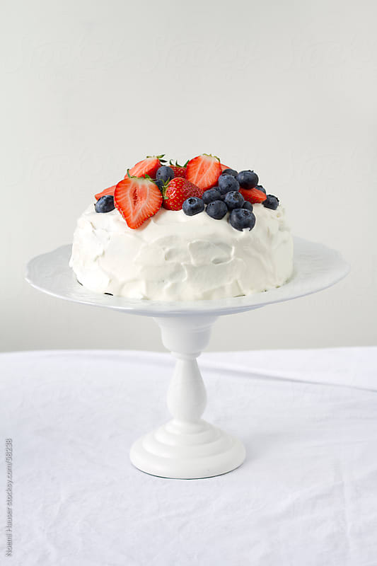Cake with berries on white cake pedestal by Noemi Hauser for Stocksy United
