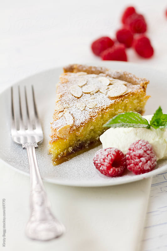 Slice of Bakewell Tart dusted with icing sugar, raspberries and cream on the side by Kirsty Begg for Stocksy United
