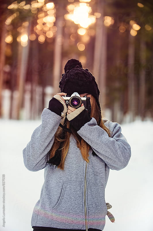Teenage girl taking a photo with a film camera outside in winter sunset light by Angela Lumsden for Stocksy United