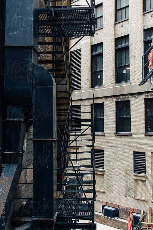 Fire escape in an alley by Gabriel (Gabi) Bucataru for Stocksy United