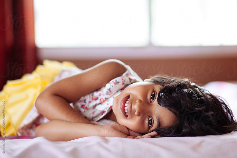 Little girl lying on bed and smiling by Saptak Ganguly for Stocksy United