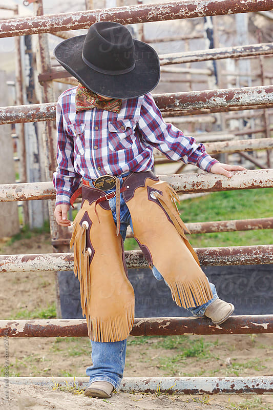 Young cowboy leaning against corral fence. by Tana Teel for Stocksy United