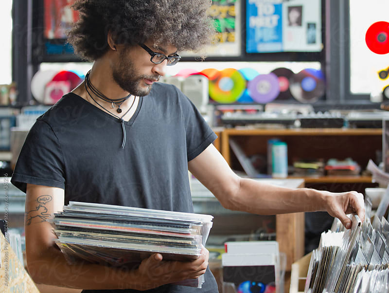 Young man browsing records in record shop by Andersen Ross Photography for Stocksy United