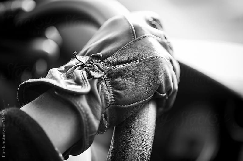 female hand in leather glove on steering wheel by Lior + Lone for Stocksy United