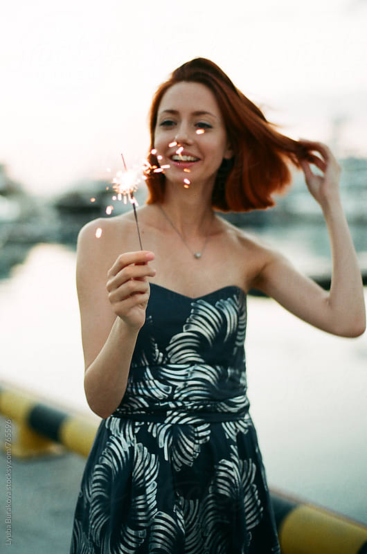 Woman holding a sparkler in front of her face by Lyuba Burakova for Stocksy United