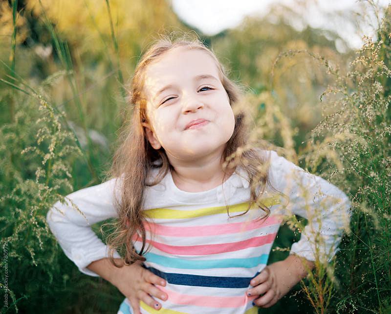 Portrait of a sassy young girl standing in a field of tall grass by Jakob for Stocksy United