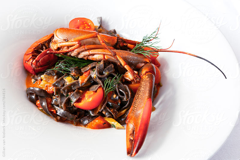 bold seafood dish with lobster and squid ink pasta by Gillian Vann for Stocksy United