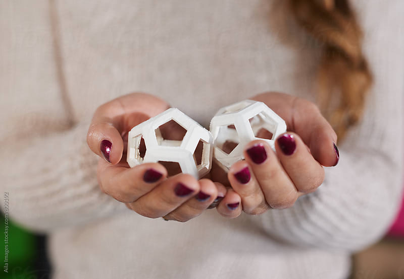 young women wearing white jumper closely holding and inspecting 3d printed hexagon design samples in beautiful manicured hands by Aila Images for Stocksy United