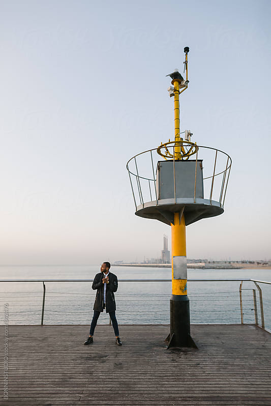 Man standing on bridge over sea. by BONNINSTUDIO for Stocksy United