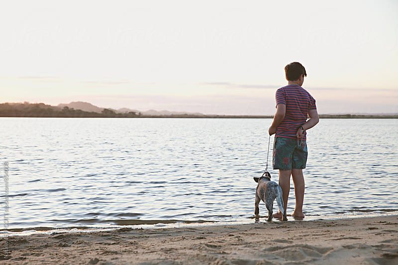 A young boy at the beach during sunset with his puppy by Natalie JEFFCOTT for Stocksy United