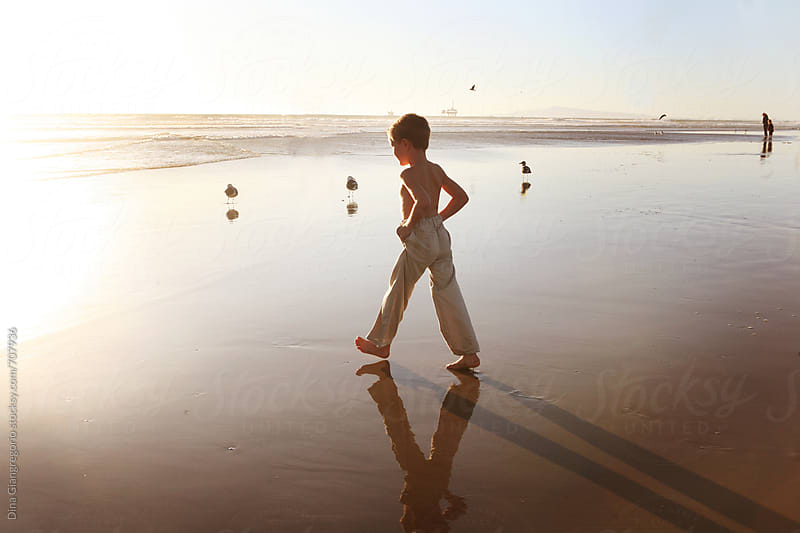 Boy Holding Pants Legs Up Walking Towards Ocean by Dina Giangregorio for Stocksy United