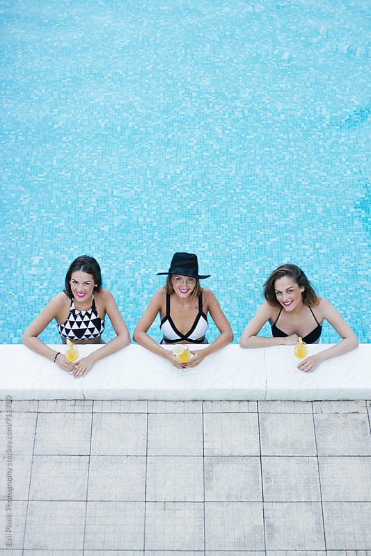 Portrait of a three beautiful female friends spending time on the swimming pool by Branislava Živić for Stocksy United