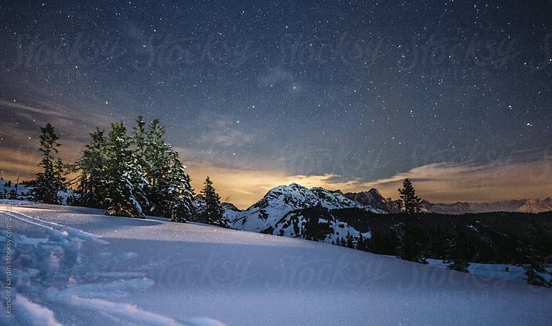 traces in snowcovered alpine landscape under starry night by Leander Nardin for Stocksy United