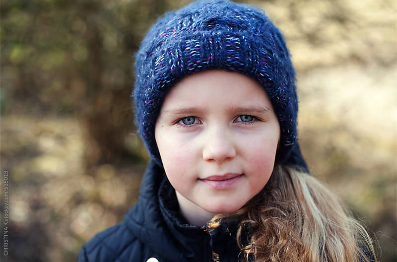 Young girl in a blue woollen hat by CHRISTINA K for Stocksy United