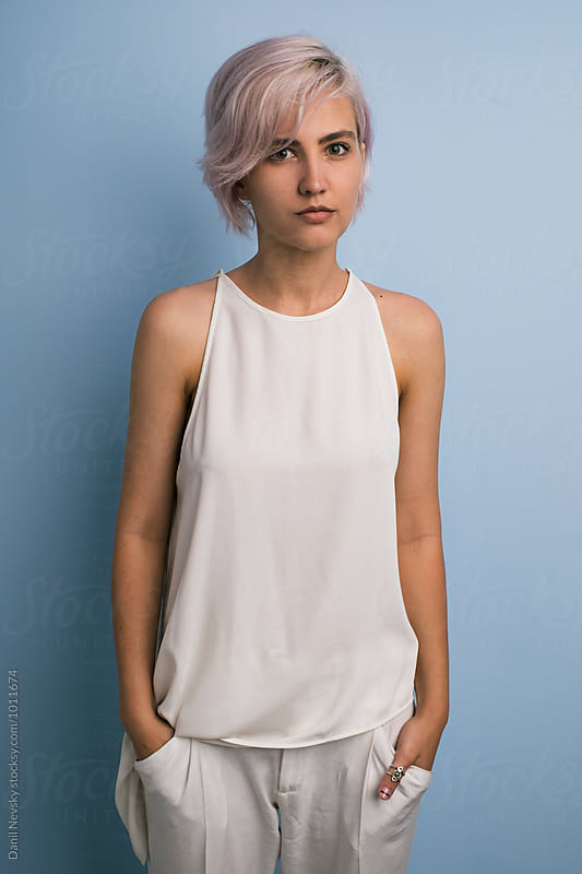 Pink-haired girl in white against of blue backround by Danil Nevsky for Stocksy United