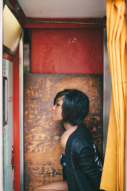 Black girl sitting in a Photo Booth  by Gabrielle Lutze for Stocksy United