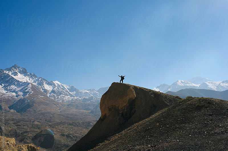 A trekker raising his arms with the mighty himalayas on the background. by Shikhar Bhattarai for Stocksy United