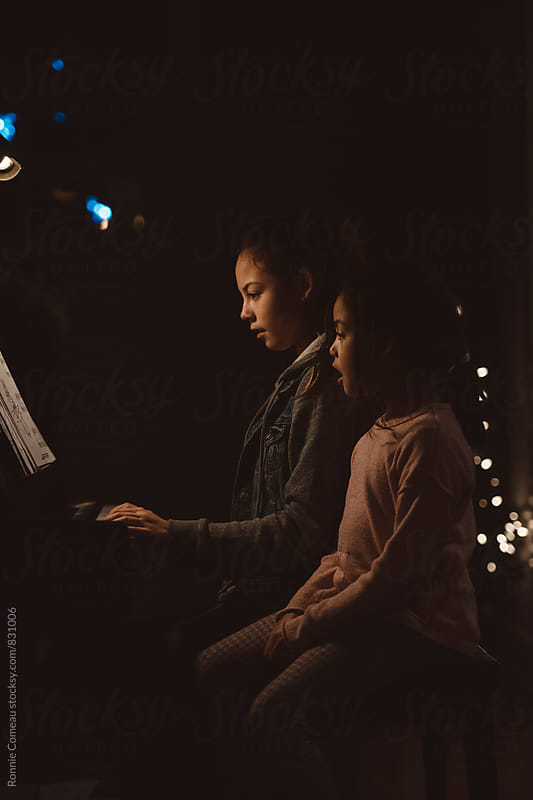 Sisters Singing And Playing Piano by Ronnie Comeau for Stocksy United