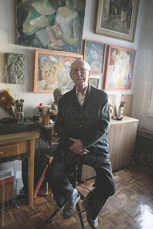 Old man sitting on his studio of painting and sculpture. by BONNINSTUDIO for Stocksy United