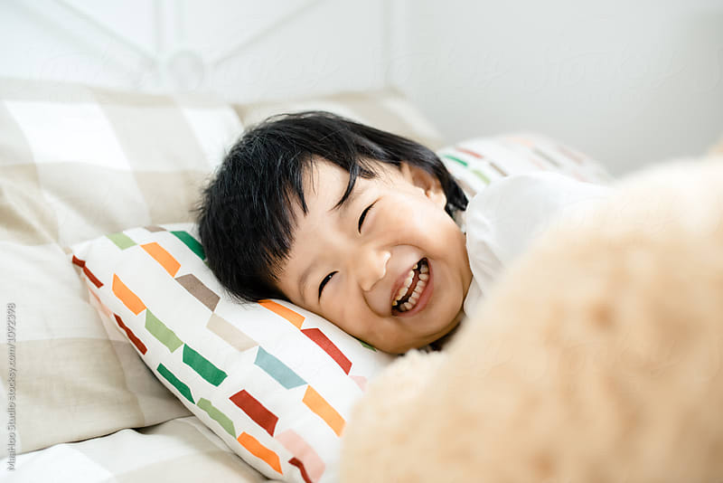 Cute toddler girl lying on bed and laughing by MaaHoo Studio for Stocksy United
