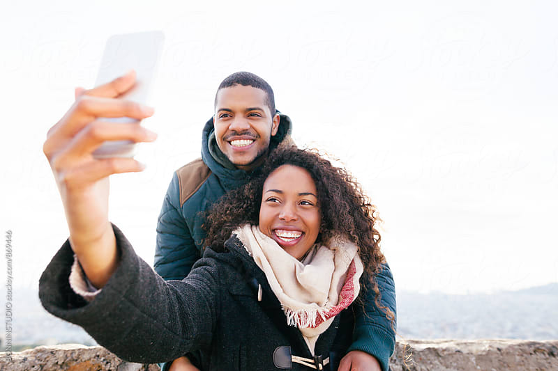 Smiling couple taking a selfie above city on winter. by BONNINSTUDIO for Stocksy United