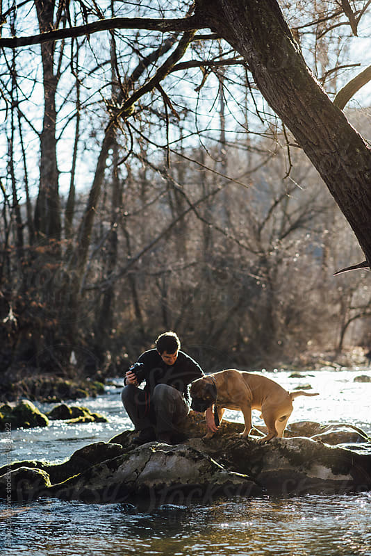 Man standing on the rocks by the river bank with his dog by Boris Jovanovic for Stocksy United