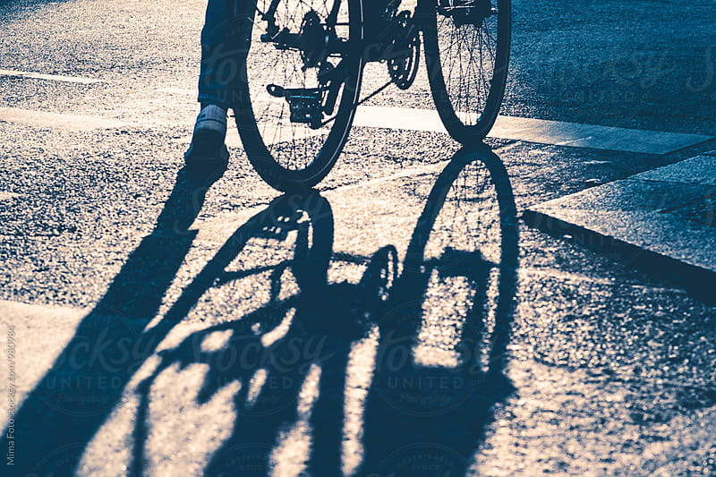Bike and shadow on traffic stop line by Mima Foto for Stocksy United