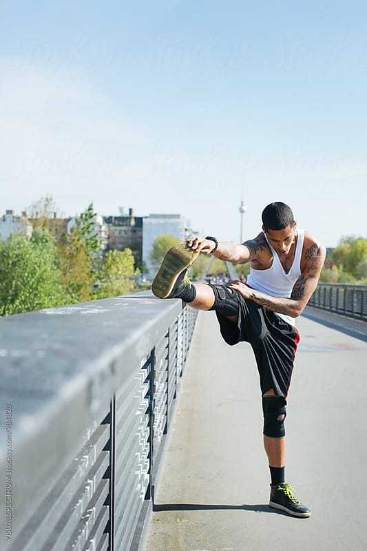 Outdoor Summer Portrait of Athletic Young Mixed Race Man Stretching Leg by Julien L. Balmer for Stocksy United