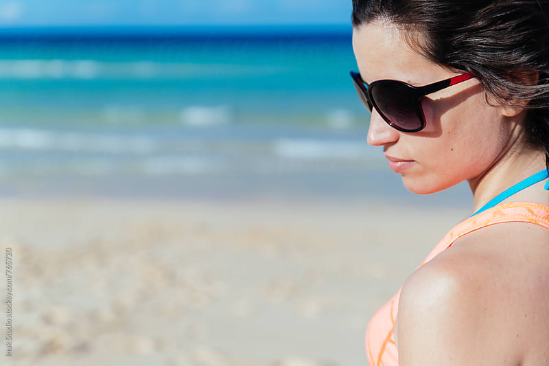 Fashion young woman looking down wearing brown sunglasses in a beach by Inuk Studio for Stocksy United