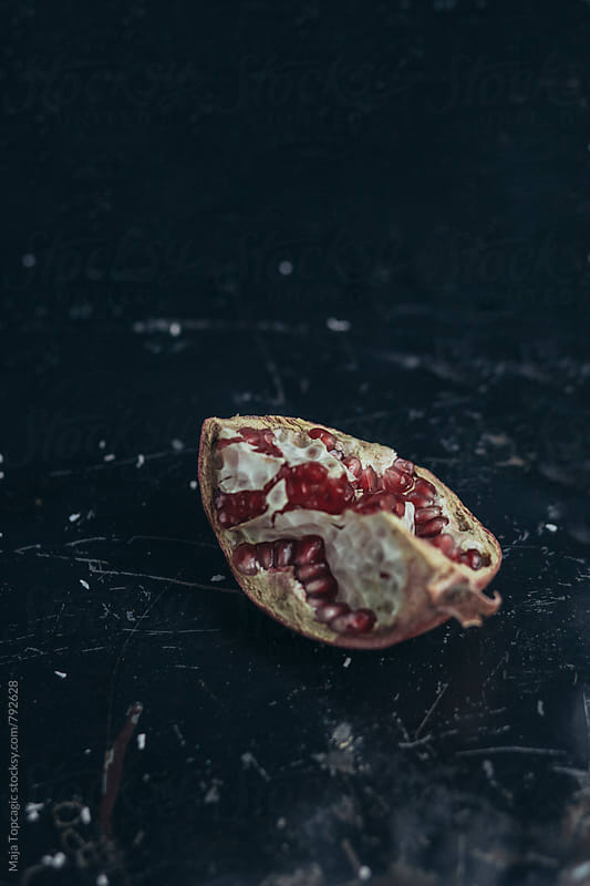 Pomegranate against a dark background by Maja Topcagic for Stocksy United
