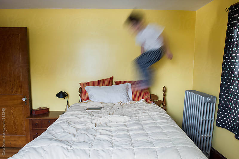 Motion blur as child bounces on the bed in his room  by Cara Dolan for Stocksy United