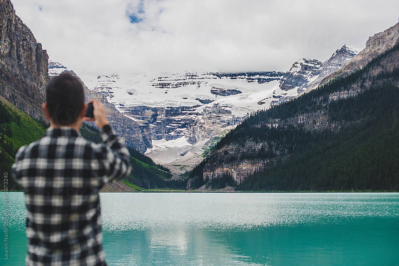 Man taking photograph of mountains in countryside by Lauren Naefe for Stocksy United