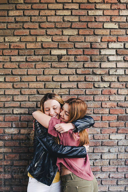 Happy best friends embracing in front of a brick wall. by BONNINSTUDIO for Stocksy United