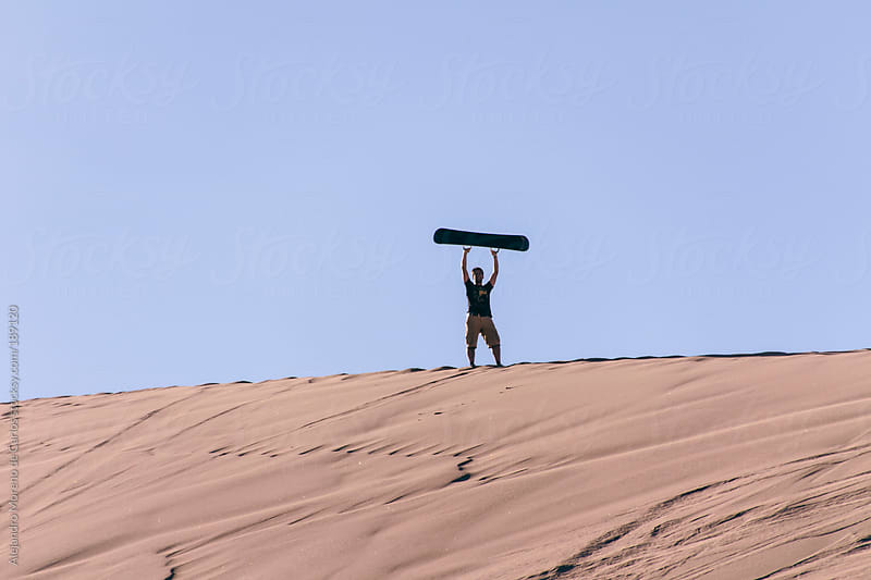 Young man with sandboard on his hands on top of a sand dune in the desert by Alejandro Moreno de Carlos for Stocksy United
