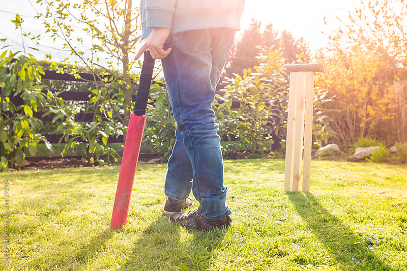 A boy with a cricket bat and stumps in his garden by Craig Holmes for Stocksy United