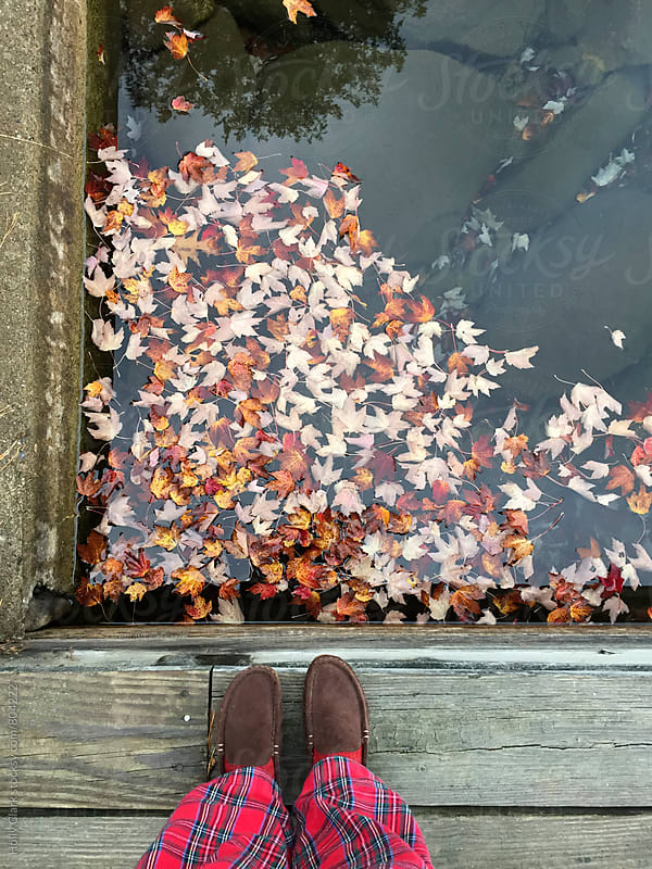Woman wearing brown slippers and red plaid pajama pants stands on a dock in autumn by Holly Clark for Stocksy United