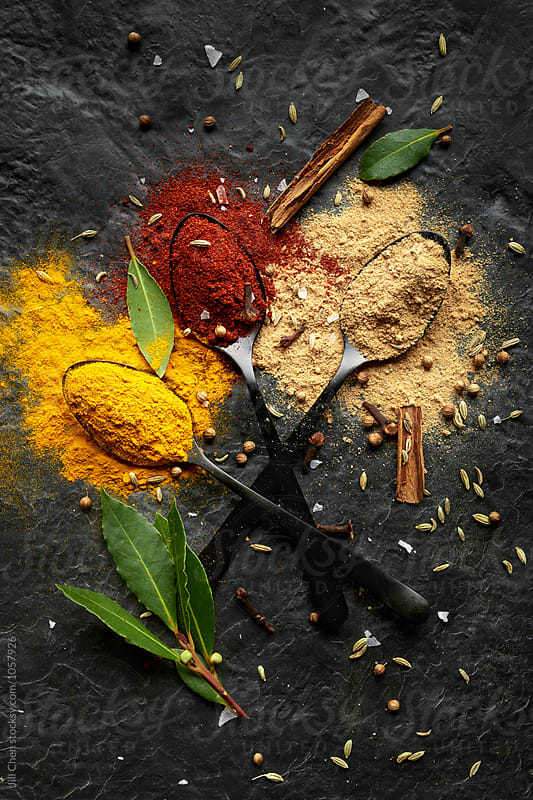 Colourful spice powder seasonings on dark background  by Jill Chen for Stocksy United