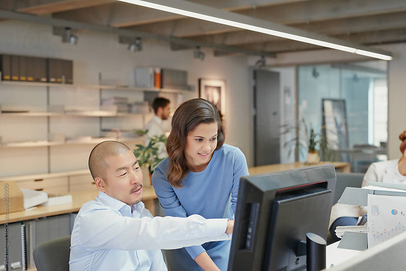 Japanese businessman team leader teaching young trainee showing data on computer monitor by Aila Images for Stocksy United