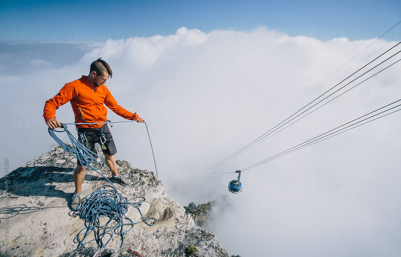Male mountaineer pulling up a rope after a climb on Table Mountain, cable car in the background by Micky Wiswedel for Stocksy United