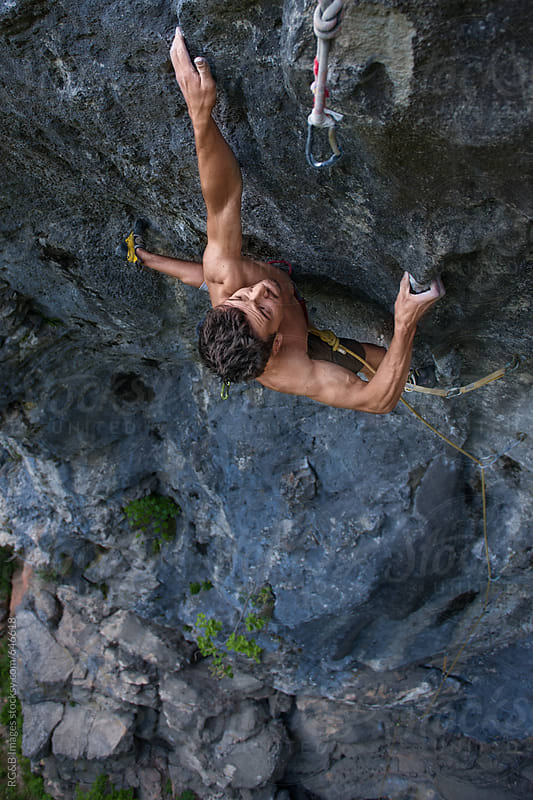 Young man climbing a steep rock wall outdoor by RG&B Images for Stocksy United