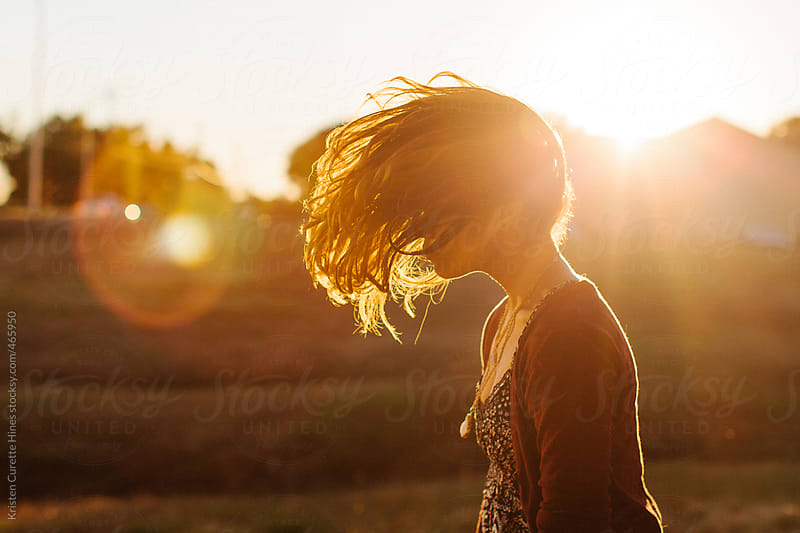 A young woman flipping her hair in the middle of a field.  by Kristen Curette Hines for Stocksy United