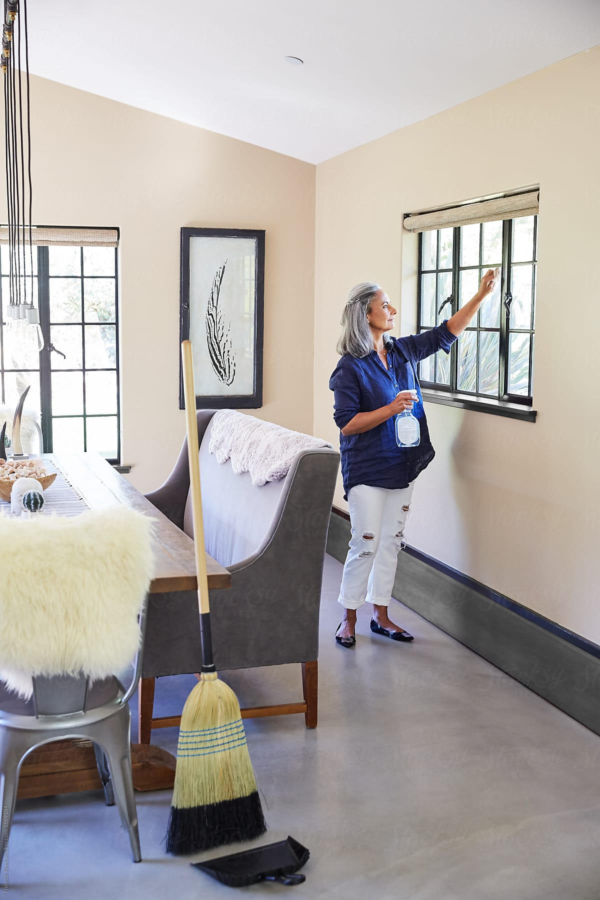 Mature Woman Cleaning Windows At Home With Non Toxic Cleaner By