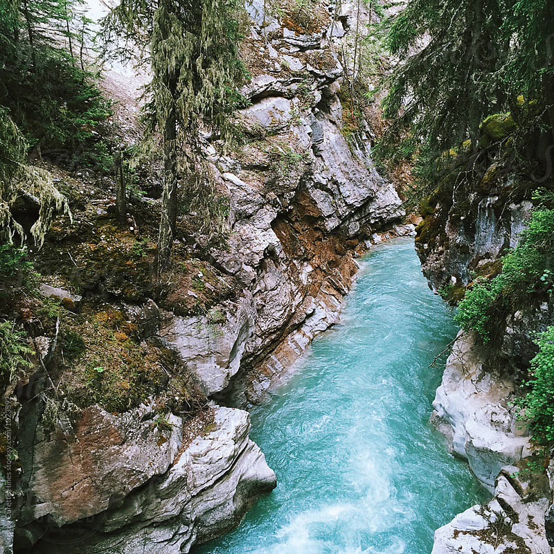 Mobile phone capture of a blue river cutting through a canyon by Kristen Curette Hines for Stocksy United