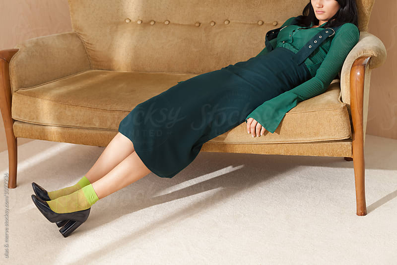 young lady relaxes on a retro couch by Ulaş and Merve for Stocksy United