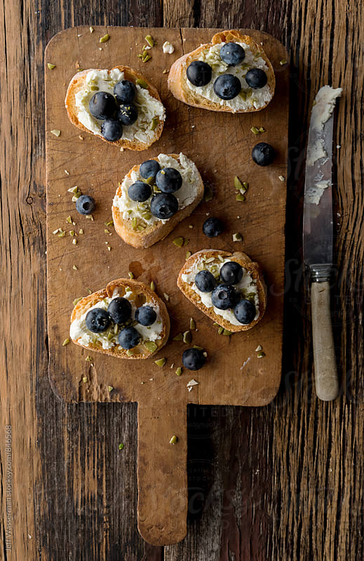 Crostini with Goat Cheese and Blueberry on Cutting Board by Jeff Wasserman for Stocksy United
