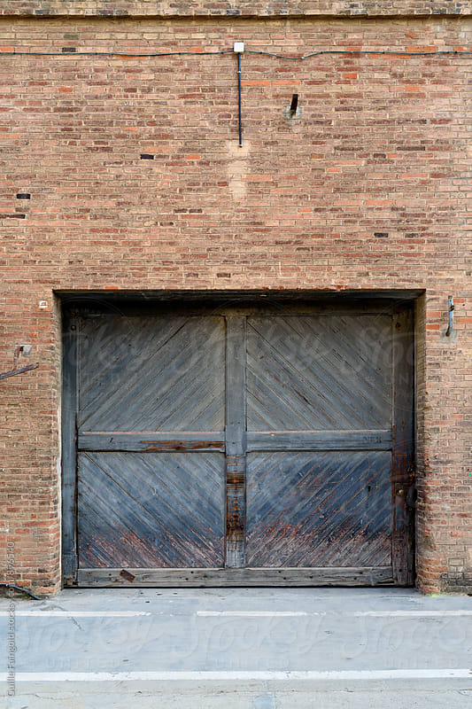 Old brick wall with wooden door by Guille Faingold for Stocksy United